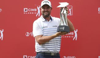 Marc Leishman of Australia poses with his trophy after winning the CIMB Classic golf tournament at Tournament Players Club (TPC) in Kuala Lumpur, Malaysia, Sunday, Oct. 14, 2018. (AP Photo/Vincent Phoon)