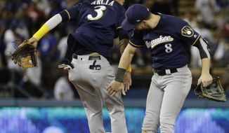Milwaukee Brewers' Orlando Arcia and Ryan Braun celebrate after Game 3 of the National League Championship Series baseball game against the Los Angeles Dodgers Monday, Oct. 15, 2018, in Los Angeles. The Brewers won 4-0 to take a 2-1 lead in the series. (AP Photo/Matt Slocum)
