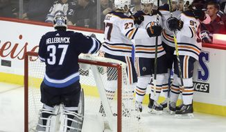 Edmonton Oilers' Milan Lucic (27), Ryan Nugent-Hopkins (93), Leon Draisaitl (29) and Connor McDavid (97) celebrate after McDavid scored on Winnipeg Jets goaltender Connor Hellebuyck (37) during the third period of an NHL hockey match, in Winnipeg, Manitoba, Tuesday, Oct. 16, 2018. (Trevor Hagan/The Canadian Press via AP)