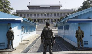 FILE - In this April 18, 2018 file photo, two South Korean soldiers, center and left, and U.S. soldier, right, stand in the southern side during a press tour at the border village of Panmunjom in the Demilitarized Zone, South Korea. North and South Korea and the U.S.-led United Nations Command on Tuesday, Oct. 16, 2018, are meeting to discuss efforts to disarm a military zone the rivals control within their shared border under a peace agreement between the Koreas. (AP Photo/Lee Jin-man, File)