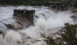 "Water from the Colorado River pours over the Max Starcke Dam, Tuesday Oct. 16, 2018, in Marble Falls, Texas. The Llano and Colorado rivers meet at Kingsland and the National Weather Service said both were experiencing ""major flooding."" A flash flood warning was in effect. (Amanda Voisard/Austin American-Statesman via AP)"