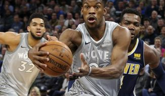 FILE - In this April 11, 2018, file photo, Minnesota Timberwolves' Jimmy Butler, center, drives to the basket ahead of Denver Nuggets' Paul Millsap, right, during the first half of an NBA basketball game in Minneapolis. Butler joined the Timberwolves for practice again on Sunday, Oct. 14, 2018, with the season opener just three days away despite his request to be traded. (AP Photo/Jim Mone, File)