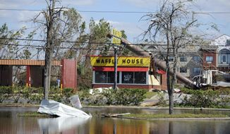 In this Sunday, Oct. 14, 2018, photo, a billboard lies atop a Waffle House restaurant after being knocked down by Hurricane Michael, in Panama City, Fla. (Carlos R. Munoz/Sarasota Herald-Tribune via AP)