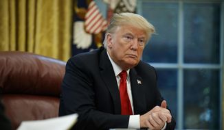 President Donald Trump listens to a question during an interview with The Associated Press in the Oval Office of the White House, Tuesday, Oct. 16, 2018, in Washington. (AP Photo/Evan Vucci)