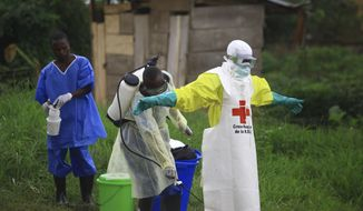 In this Sunday, Sept 9, 2018, photo, a health worker sprays disinfectant on his colleague after working at an Ebola treatment center in Beni, Eastern Congo. (AP Photo/Al-hadji Kudra Maliro) ** FILE **