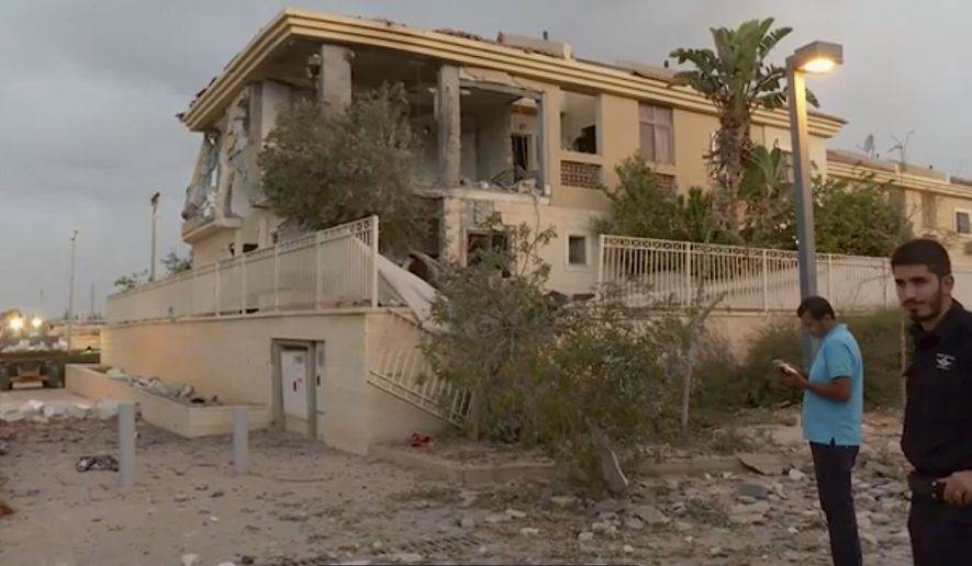 In this image made from video, police inspect the damage to a building from a rocket, Wednesday, Oct. 17, 2018, in Beersheba, Israel. The Israeli military says a rocket fired from Gaza made a direct hit on a home in southern Israel. Its the first rocket attack against Israel in months and the first that hit an Israeli home in Beersheba since the 2014 war between Israel and Gazas militant Hamas rulers. (KAN via AP)