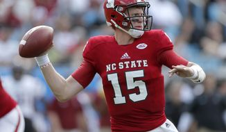FILE - In this Sept. 2, 2017, file photo, North Carolina State's Ryan Finley (15) looks for an open receiver against South Carolina during the first half of an NCAA college football game in Charlotte, N.C. Coach Dino Babers has led Syracuse to a surprising 4-2 record midway through the season, while Clemson and North Carolina State, led by quarterback Ryan Finley, are undefeated entering a big showdown this week. All drew attention in midseason voting by AP writers covering the 14 ACC teams. (AP Photo/Bob Leverone, File)