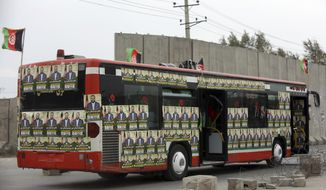 A campaign bus is covered with posters of parliamentary candidate, Dr. Abdul Baqi Ameen, ahead of Parliamentary elections scheduled for Oct. 20, during a campaign rally in Kabul, Afghanistan, Tuesday, Oct. 16, 2018. (AP Photo/Rahmat Gul)