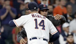 Houston Astros manager AJ Hinch, left, and Boston Red Sox manager Alex Cora hug before Game 3 of a baseball American League Championship Series on Tuesday, Oct. 16, 2018, in Houston. (AP Photo/David J. Phillip) **FILE**