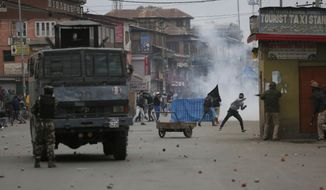 Kashmiri Muslim protesters clash with Indian government forces during the fourth phase of local elections in Srinagar, Indian controlled Kashmir, Tuesday, Oct. 16, 2018. India says the polls are a vital grass roots exercise to boost development and address civic issues. Political separatist leaders and armed rebel groups who challenge India's sovereignty over Kashmir have called for a boycott, saying the polls are an illegitimate exercise under military occupation. Authorities have deployed more than 40,000 additional soldiers in what is already one of world's most heavily militarised regions to guard the voting for urban and village councils. (AP Photo/Mukhtar Khan)