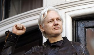 In this file photo dated Friday, May 19, 2017, WikiLeaks founder Julian Assange looks out from the balcony of the Ecuadorian Embassy in London. (AP Photo/Matt Dunham, FILE)