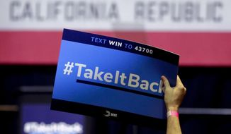 In this Thursday, Oct. 4, 2018, photo a supporter holds up a sign for Gil Cisneros, a candidate who is running for a U.S. House seat in the 39th District in California, at a rally on the Cal State Fullerton campus in Fullerton, Calif. For decades, Orange County, California, was known as a Republican stronghold but times have changed. A sign of the change is in the 39th District, where, Young Kim, a Korean immigrant Republican is running against Cisneros, a Hispanic Democrat. (AP Photo/Chris Carlson)