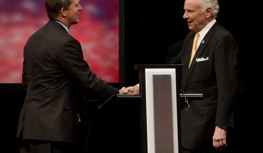 Democratic state Rep. James Smith and Republican Gov. Henry McMaster shake hands prior to the South Carolina governor debate, Wednesday, Oct. 17, 2018 at Francis Marion University Performing Arts Center in Florence, S.C. (Andrew J. Whitaker/The Post And Courier via AP)