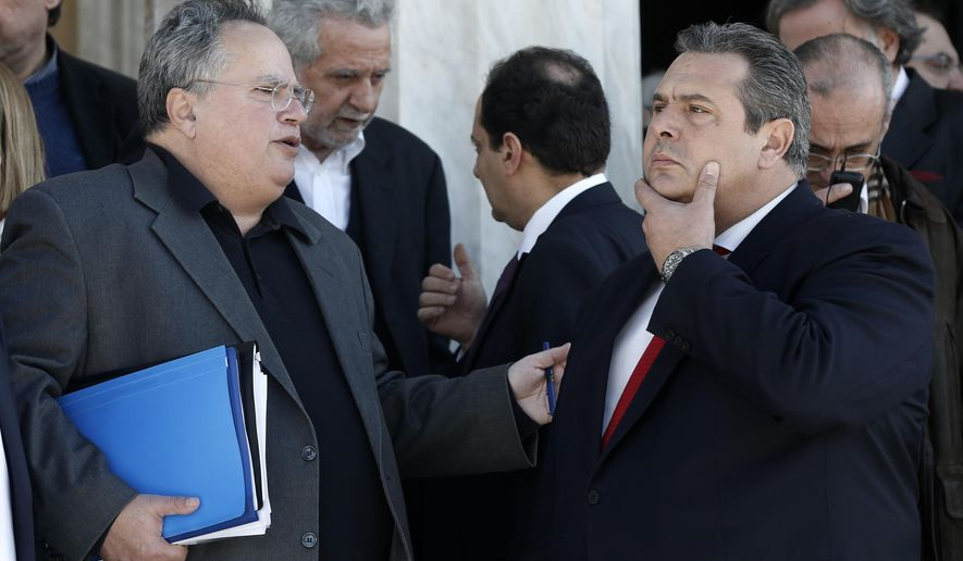 FILE - In this Wednesday, Jan. 28, 2015 file photo, Greece's Foreign Minister, left, Nikos Kotzias, speaks with Defense Minister Panos Kammenos before a group picture of the new government outside the Parliament in Athens. Greek Foreign Minister Nikos Kotzias has resigned, on Wednesday, Oct. 17, 2018, following a disagreement with the defense minister over the handling of a recent deal which would change Macedonia's name in exchange for Greece dropping its objections to the country joining NATO. (AP Photo/Petros Giannakouris, File)