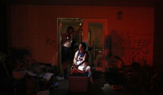 Tasha Hughes, bathes her daughter, Madison, 4, as Jeffrey Dumich holds a flashlight outside their room at the damaged American Quality Lodge where they continue to live without power in the aftermath of Hurricane Michael, in Panama City, Fla., Tuesday, Oct. 16, 2018. Simply getting through the day is a struggle at the low-rent motel where dozens of people are living in squalor amid destruction left by the hurricane. (AP Photo/David Goldman)