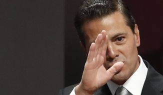 FILE - In this Sept. 3, 2018 file photo, Mexican President Enrique Pena Nieto waves to guests as he arrives to deliver his sixth and final State of the Nation address at the National Palace in Mexico City.  The Pena Nieto adminsitration is looking to protect itself from future investigation of corruption once it leaves power. (AP Photo/Rebecca Blackwell, File)