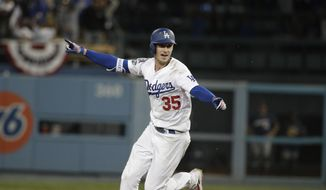 Los Angeles Dodgers' Cody Bellinger reacts after hitting a walk-off hit during the 13th inning of Game 4 of the National League Championship Series baseball game against the Milwaukee Brewers Tuesday, Oct. 16, 2018, in Los Angeles. The Dodgers won 2-1 to tie the series at 2-2. (AP Photo/Jae Hong)