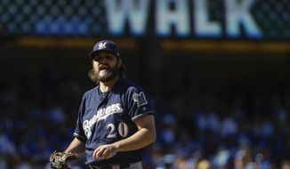 Milwaukee Brewers starting pitcher Wade Miley reacts after giving up a walk during the first inning of Game 5 of the National League Championship Series baseball game against the Los Angeles Dodgers Wednesday, Oct. 17, 2018, in Los Angeles. (AP Photo/Matt Slocum)