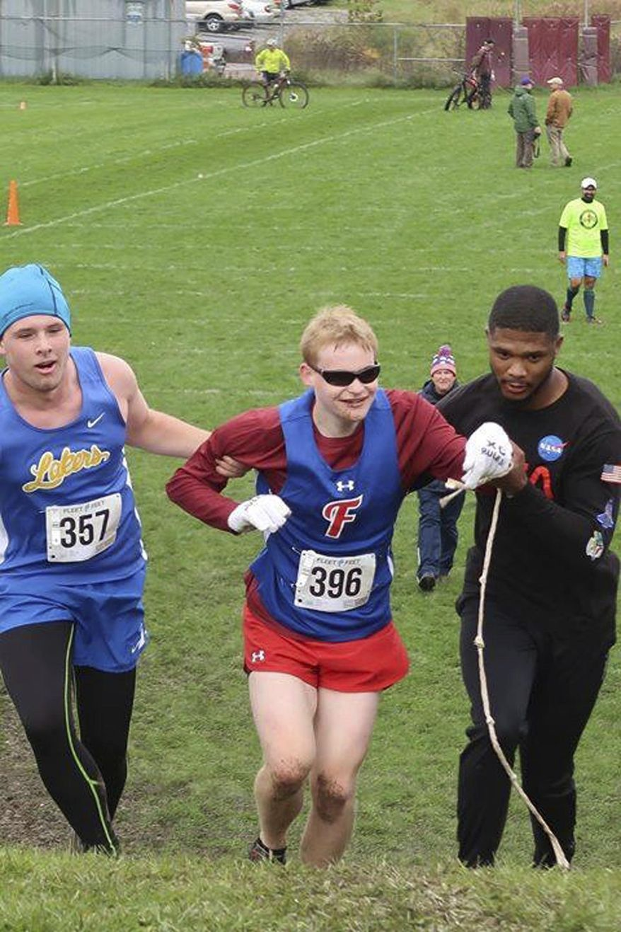 In this Saturday, Oct. 13, 2018 photo provided by Karen Wylie, Cazenovia High School sophomore Jake Tobin, left, helps Fairport High School senior Luke Fortner, center, during a cross country race in Auburn, N.Y. Fortner, who is legally blind, fell towards the end of the race but was assisted by Tobin, and Jerry Thompson, right, his running aide. The three then crossed the finish line together. (Karen Wylie via AP)
