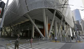 FILE - In this Sept. 27, 2018, file photo, people stop to look at the closed Salesforce Transit Center in San Francisco. The general contractor that managed San Francisco's troubled $2.2 billion transit terminal is suing the agency in charge of the project, alleging faulty design and and mismanagement led to construction delays and costs overruns that cost the company $150 million. (AP Photo/Eric Risberg, File)