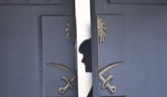 A Consulate staff is seen behind the entrance of the Saudi Arabia's Consulate in Istanbul, Wednesday, Oct. 17, 2018. On Wednesday a pro-government Turkish newspaper published a report made from what they described as an audio recording of Saudi writer and journalist Jamal Khashoggi's alleged torture and slaying at the Saudi Consulate in Istanbul. (AP Photo/Petros Giannakouris)