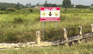 """A sign that says """"Dangerous"""" stands in an area of Bien Hoa air base in Vietnam where Defense Secretary Jim Mattis was being briefed nearby on U.S. efforts, set to begin by December, to decontaminate soil poisoned with dioxin from Agent Orange, Tuesday, Oct. 16, 2018, in Bien Hoa, Vietnam. The sign stands in an area of the base where Agent Orange contaminated the soil. U.S. forces stored the Agent Orange at this base during the Vietnam War. (AP Photo/Robert Burns)"""