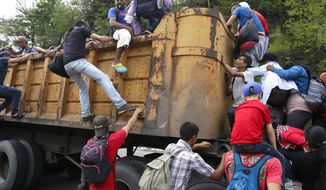 "Honduran migrants bound for the U.S climb into a truck bed in Zacapa, Guatemala, part of a ""caravan"" that's sparked intense media coverage. (Associated Press)"
