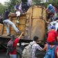 """Honduran migrants bound for the U.S climb into a truck bed in Zacapa, Guatemala, part of a """"caravan"""" that's sparked intense media coverage. (Associated Press)"""