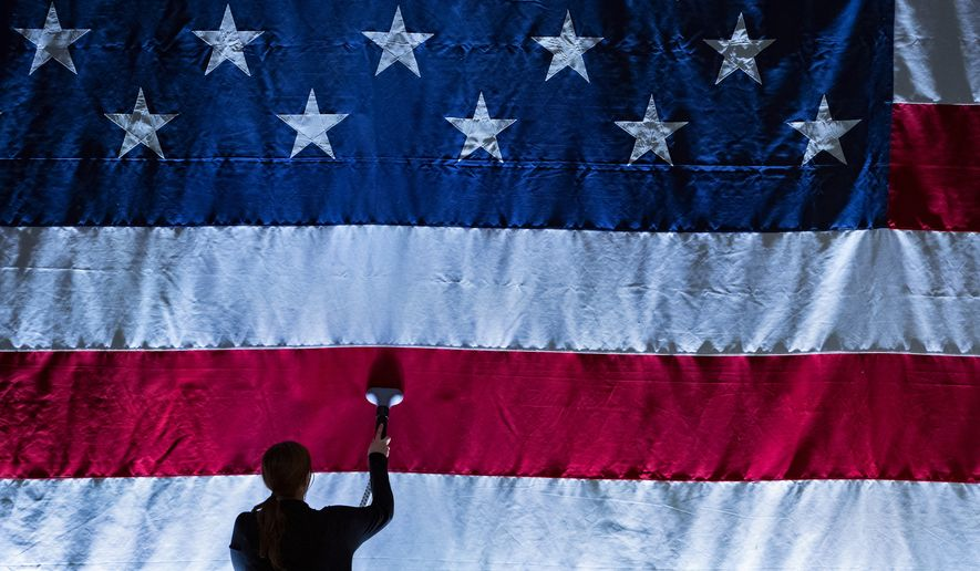 An American flag is steam ironed before the 73rd Annual Alfred E. Smith Memorial Foundation Dinner Thursday, Oct. 18, 2018, in New York. (AP Photo/Craig Ruttle)