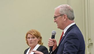 Republican U.S. Rep. Kevin Cramer, front, makes a point as North Dakota Democratic U.S. Sen. Heidi Heitkamp listens during the U.S. Senate Candidate Debate on Thursday night, Oct. 18, 2018, in Bismarck, N.D. The debate was sponsored by the North Dakota Newspaper Association. (Tom Stromme/The Bismarck Tribune via AP)