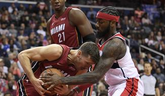 Washington Wizards guard John Wall, right, battles for the ball against Miami Heat guard Goran Dragic, left, of Slovenia, during the first half of an NBA basketball game, Thursday, Oct. 18, 2018, in Washington. (AP Photo/Nick Wass)