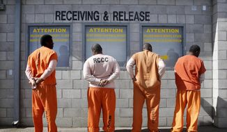 In this Feb. 20, 2014, file photo, prisoners from Sacramento County await processing after arriving at the Deuel Vocational Institution in Tracy, Calif. California will reconsider life sentences for thousands of nonviolent third-strike criminals by allowing them to seek parole under a ballot measure approved by voters two years ago. Court documents obtained by the Associated Press on Thursday, Oct. 18, 2018, show Gov. Jerry Brown's administration will include the repeat offenders in Proposition 57's early release program. (AP Photo/Rich Pedroncelli, file)