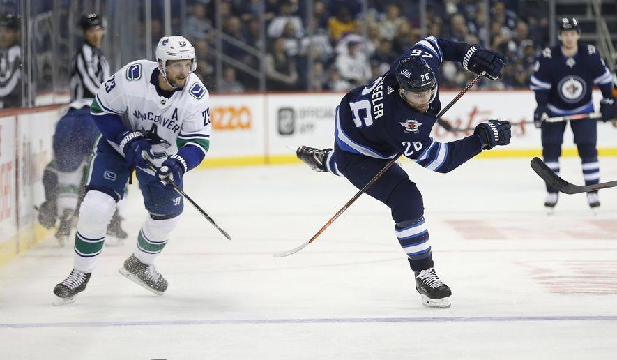 Winnipeg Jets' Blake Wheeler (26) works his way around Vancouver Canucks' Alexander Edler (23) during second period NHL hockey action in Winnipeg, Manitoba, Thursday, Oct. 18, 2018. (John Woods/The Canadian Press via AP)