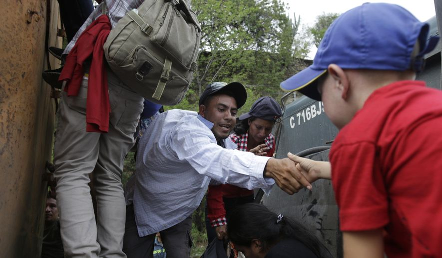 Honduran migrants walking to the U.S. climb on to the space between the cab and bed of a trailer in Zacapa, Guatemala, Wednesday, Oct. 17, 2018. The group of some 2,000 Honduran migrants hit the road in Guatemala again Wednesday, hoping to reach the United States despite President Donald Trump's threat to cut off aid to Central American countries that don't stop them. (AP Photo/Moises Castillo)