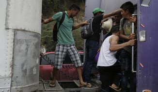 Honduran migrants who are walking to the U.S. as a group climb on to the space between a truck driver's cab and trailer, as they get a free ride through Zacapa, Guatemala, Wednesday, Oct. 17, 2018. The group of some 2,000 Honduran migrants hit the road in Guatemala again Wednesday, hoping to reach the United States despite President Donald Trump's threat to cut off aid to Central American countries that don't stop them. (AP Photo/Moises Castillo)