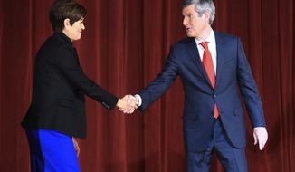 From left, Iowa Gov. Kim Reynolds shakes hands with Democratic candidate Fred Hubbell during the gubernatorial debate at Morningside College in Sioux City, Iowa on Wednesday, Oct. 17, 2018. (Justin Wan/Sioux City Journal via AP)