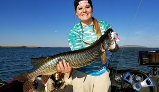 In this August 2018 photo Kelli Fundingsland holds a tiger muskie she caught and later released in Minot, N.D. Tiger muskies are coming of age in Lake Audubon.  (Kim Fundingsland /Minot Daily News via AP)
