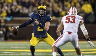 FILE - In this Oct. 13, 2018, file photo, Michigan quarterback Shea Patterson (2) tries to scramble away from Wisconsin inside linebacker T.J. Edwards (53) in the second quarter of an NCAA college football game, in Ann Arbor, Mich. No. 6 Michigan is preparing to play No. 24 Michigan State with dual-threat quarterback Shea Patterson working on the split-second decisions he makes, choosing when to pass, run or throw the ball away. (AP Photo/Tony Ding, File)
