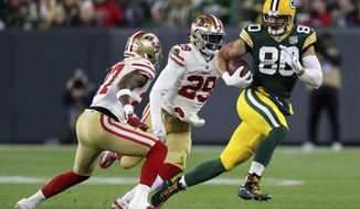 FILE - In this Monday, Oct. 15, 2018, file photo, Green Bay Packers tight end Jimmy Graham (80) runs against San Francisco 49ers free safety Adrian Colbert (27) and strong safety Jaquiski Tartt (29) after making a catch during the second half of an NFL football game in Green Bay, Wis. Two passions fuel Green Bay Packers tight end Jimmy Graham: flying and football. (AP Photo/Matt Ludtke, File)