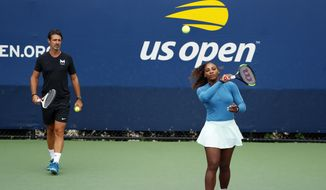 """FILE - In this Aug. 31, 2018, file photo, Serena Williams walks on a practice court with her coach, Patrick Mouratoglou, during the third round of the U.S. Open tennis tournament,  in New York. Serena Williams' coach says in-match coaching should be allowed in tennis to help the sport's popularity. Mouratoglou, who admitted he used banned hand signals to try to help Williams during her loss in the U.S. Open final, wrote Thursday, Oct. 18, 2018, in a posting on Twitter that legalizing coaching and making it part of the spectacle would let """"viewers enjoy it as a show.""""(AP Photo/Adam Hunger, File)"""