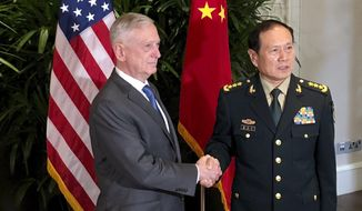 U.S. Defense Secretary Jim Mattis, left, meets Chinese Defense Minister Wei Fenghe in Singapore Thursday, Oct. 18, 2018. After a rocky few months, Pentagon officials say they sense that relations with the Chinese military may be stabilizing. (AP Photo/Robert Burns)