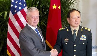 U.S. Defense Secretary Jim Mattis, left, meets Chinese Defense Minister Wei Fenghe in Singapore Thursday, Oct. 18, 2018. After a rocky few months, Pentagon officials say they sense that relations with the Chinese military may be stabilizing. (AP Photo/Robert Burns) ** FILE **