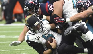 FILE - In this Jan. 3, 2016, file photo, Jacksonville Jaguars quarterback Blake Bortles (5) is sacked by Houston Texans defensive end J.J. Watt (99) during the second half of an NFL football game in Houston. The Jaguars are trying to straighten out their turnover issue ahead of their game agains the Houston Texans on Sunday, Oct. 21, 2018. The Jags have been careless with the football through six games and have done considerably less to create fumbles and interceptions. The result is Jacksonville sits next to last in turnover margin at minus-9. Finding a way to end the trend against the Houston Texans could be the difference between first place in the AFC South and a three-game losing streak. (AP Photo/Eric Christian Smith, File)