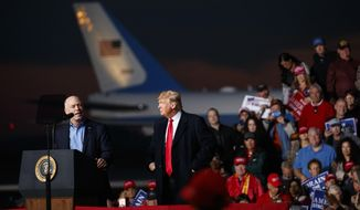 Rep. Greg Gianforte, R-Mont., speaks as President Donald Trump stands right during a campaign rally at Minuteman Aviation Hangar, Thursday, Oct. 18, 2018, in Missoula, Mont. (AP Photo/Carolyn Kaster)