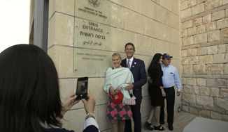 "FILE - In this May 14, 2018 file photo, visitors have a photo taken at the entrance to the new U.S. Embassy in Jerusalem. The U.S. said Thursday Oct. 18, 2018 that it is placing its main diplomatic mission to the Palestinians under the authority of its embassy to Israel. The State Department said Thursday that merging the Jerusalem Consulate with the newly opened Jerusalem Embassy will achieve ""significant efficiencies."" But the move also has symbolic significance, by in effect downgrading the standing of the consulate. (AP Photo/Sebastian Scheiner, File)"