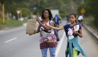 "In this Sept. 2, 2018, file photo, Venezuelan Sandra Cadiz holds up her handmade sign carrying the Spanish message: ""Blessed driver, please help us with a ride,"" as her 10-year-old daughter Angelis stands with her on the road leaving Giron, Colombia, as they make their way to Peru. As rising numbers of Venezuelans flee, those who cannot afford a plane or bus ticket out are going by foot. (AP Photo/Ariana Cubillos)"