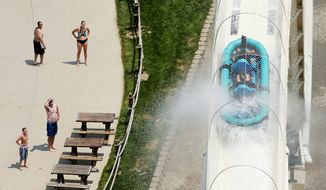 """FILE - In this July 9, 2014, file photo, riders are propelled by jets of water as they go over a hump while riding a water slide called """"Verruckt"""" at Schlitterbahn Water Park in Kansas City, Kan. Testimony has concluded in the trial of two maintenance workers at the water park who are accused of deliberately misleading investigators after a 10-year-old boy was decapitated on the waterslide. Deliberations will begin Thursday, Oct. 18, 2018 after closing arguments are made in the case against David Hughes and John Zalsman. (AP Photo/Charlie Riedel, File)"""