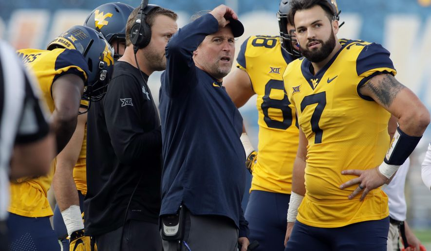 FILE - In this Sept. 22, 2018, file photo, West Virginia head coach Dana Holgorsen and quarterback Will Grier (7) talk during a timeout in the first half of an NCAA college football game against Kansas State in Morgantown, W.Va. The Mountaineers were thoroughly outplayed in a 30-14 loss at Iowa State last Saturday. Now, West Virginia (5-1, 3-1 Big 12) must use its final bye week to try to fix what went wrong.  (AP Photo/Raymond Thompson, File)