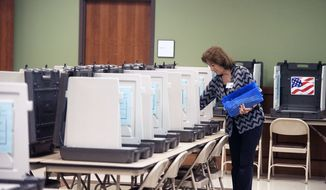 Nacogdoches County Elections Commission worker Peggy Avant doles out pens among voter booths set up at the county courthouse annex ahead of early voting opening on Monday, Friday, Oct. 19, 2018 in Nacogdoches, Texas. (Tim Monzingo/The Daily Sentinel via AP)  **FILE**