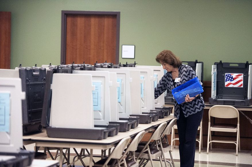 Nacogdoches County Elections Commission worker Peggy Avant doles out pens among voter booths set up at the county courthouse annex ahead of early voting opening on Monday, Friday, Oct. 19, 2018 in Nacogdoches, Texas. (Tim Monzingo/The Daily Sentinel via AP)